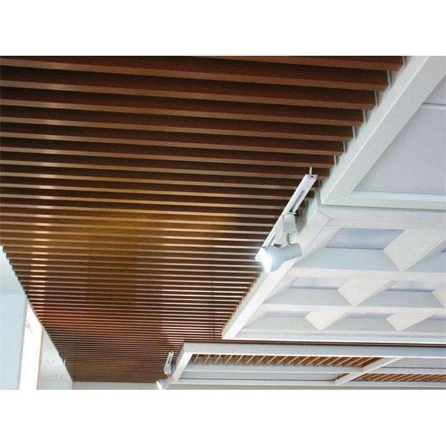 木纹条形铝格栅吊顶是一种装饰性垂帘型吊顶天花,线条明快飘逸,整体通透,祥和,色泽丰富。选用适当的高度,以适当视觉角度,能产生幕布效果,使得设计变化万千,效果美观。当的高度,以适当视角角度,你那个产生幕布效果,其它维修限制较少,令设计变化万千,整个建筑空间宽畅通透。安装铝方通都可以选择不同的高度和间距,可一高一低,一疏一密,加上合理的颜色搭配,令设计千变万化,能够设计出不同的装饰效果。同时,由于铝方通是通透式的,可以把灯具,空调系统,消防设备置于天花板内,以到达整体一致的的完美视觉效果。  通道木纹条形铝格